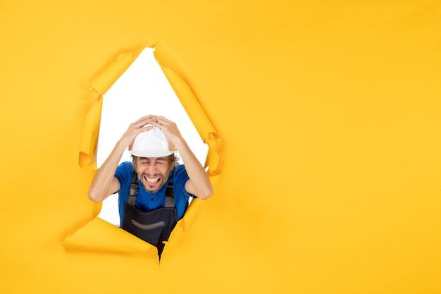Construtor masculino de vista frontal de uniforme em fundo amarelo