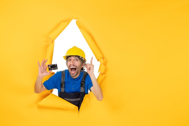 Construtor masculino de vista frontal de uniforme segurando um cartão do banco preto sobre fundo amarelo