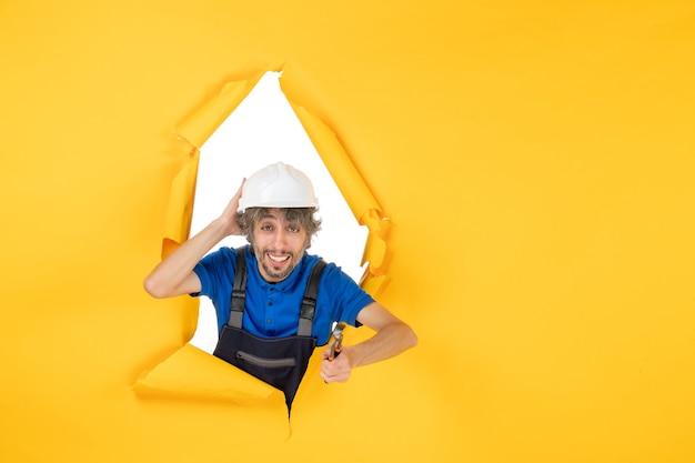 Construtor masculino de vista frontal segurando um alicate em fundo amarelo