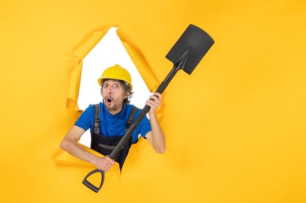 Construtor masculino de vista frontal uniforme segurando uma pá sobre fundo amarelo claro