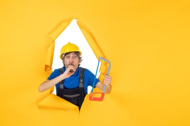 Construtor masculino de vista frontal uniforme segurando uma serra sobre fundo amarelo