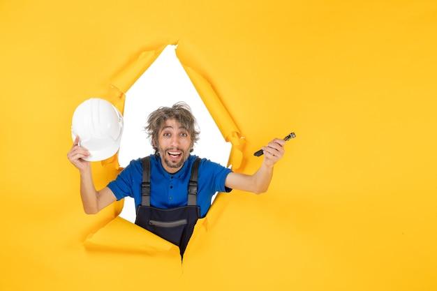 Construtor masculino de vista frontal uniformizado segurando um alicate em fundo amarelo