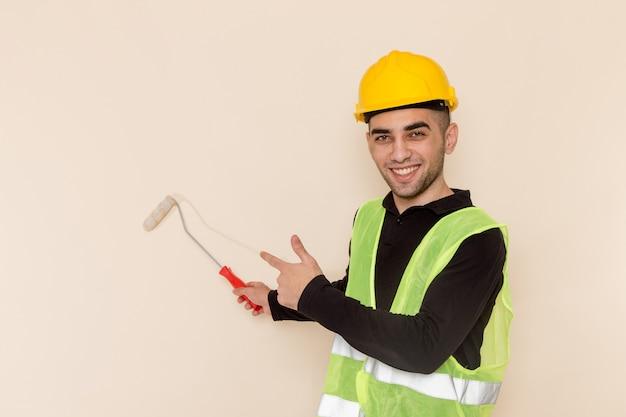 Construtor masculino em capacete amarelo pintando paredes no fundo claro