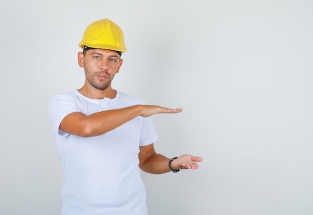 Construtor masculino em t-shirt branca, capacete de segurança mostrando gesto de tamanho grande, vista frontal.