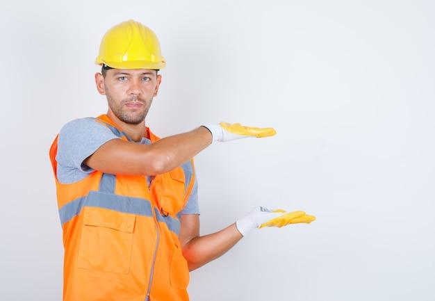 Construtor masculino em uniforme, capacete, luvas mostrando sinal de grande ou pequeno tamanho, vista frontal.