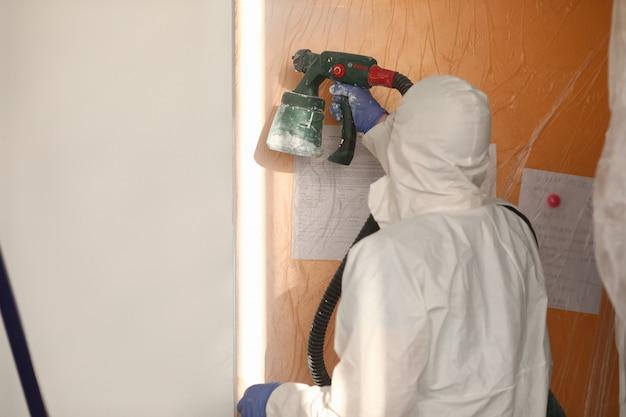 Construtor masculino em uniforme, pistola de tinta na parede