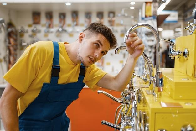 Construtor masculino escolhendo água da torneira na loja de ferragens. construtor de uniforme olha as mercadorias na loja de bricolage