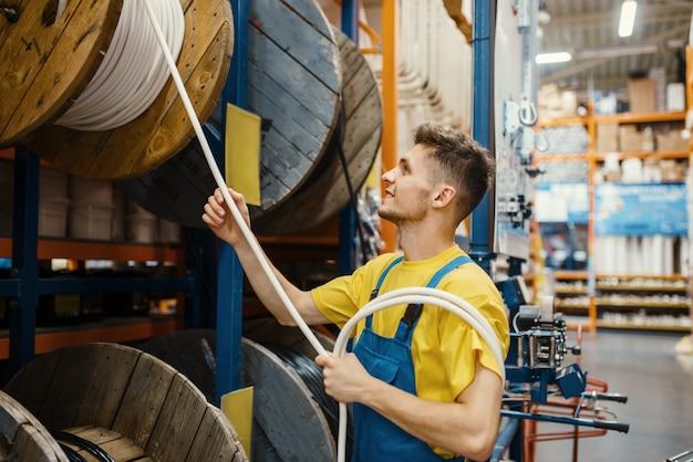 Construtor masculino escolhendo fios na prateleira da loja de ferragens. construtor de uniforme olha as mercadorias na loja de bricolage