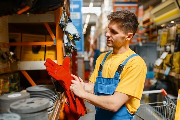 Construtor masculino escolhendo luvas na prateleira da loja de ferragens. construtor de uniforme olha as mercadorias na loja de bricolage