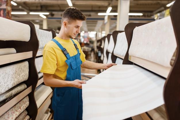 Construtor masculino escolhendo papéis de parede na loja de ferragens. construtor de uniforme olha as mercadorias na loja de bricolage