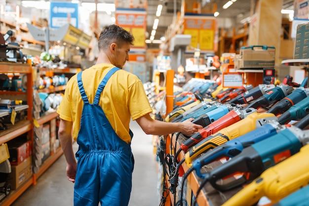 Construtor masculino escolhendo rebarbadora na prateleira da loja de ferragens. construtor de uniforme olha as mercadorias na loja de bricolage