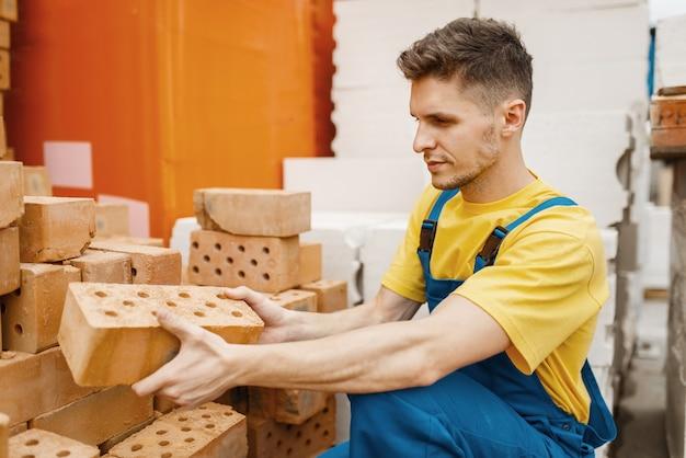 Construtor masculino escolhendo tijolos na loja de ferragens. construtor de uniforme olha as mercadorias na loja de bricolage