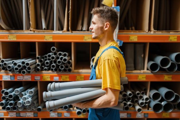 Construtor masculino escolhendo tubulação em loja de ferragens