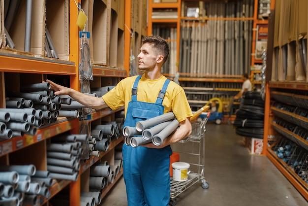 Construtor masculino escolhendo tubulação na prateleira da loja de ferragens. construtor de uniforme olha as mercadorias na loja de bricolage