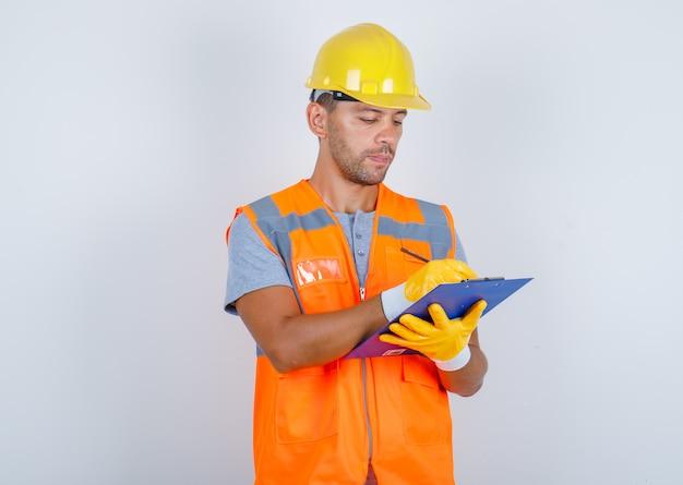Construtor masculino fazendo anotações na prancheta de uniforme, capacete, luvas e parecendo ocupado, vista frontal