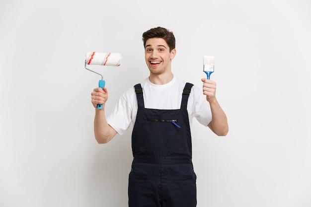 Construtor masculino feliz segurando rolo de tinta e pincel enquanto sobre a parede cinza