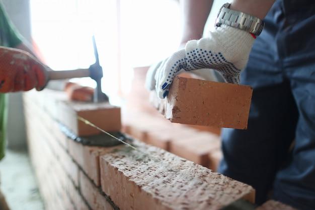 Construtor masculino mão em luvas segurando