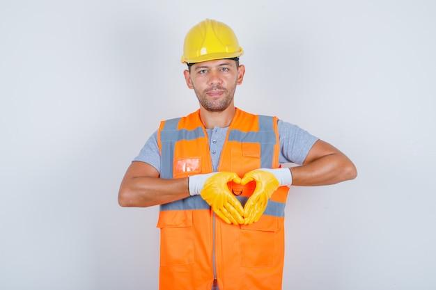 Construtor masculino mostrando a forma e o símbolo do coração com as mãos de uniforme e parecendo feliz, vista frontal.