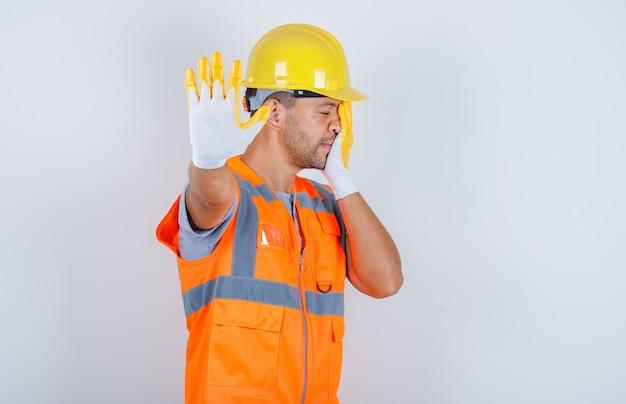 Construtor masculino mostrando parada para câmera de uniforme, capacete, luvas, vista frontal.