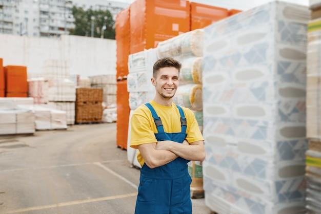 Construtor masculino nas paletes de material de isolamento em loja de ferragens. construtor de uniforme olha as mercadorias na loja de bricolage
