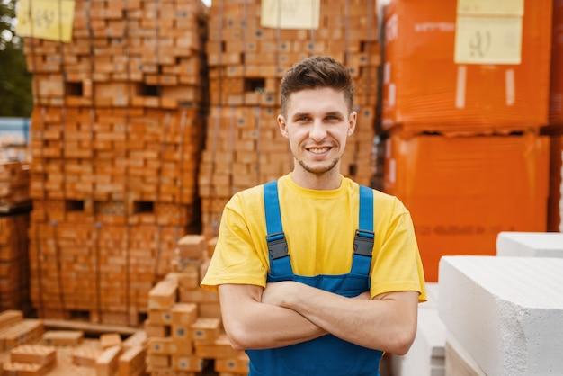 Construtor masculino nas paletes de tijolos na loja de ferragens. construtor de uniforme olha as mercadorias na loja de bricolage