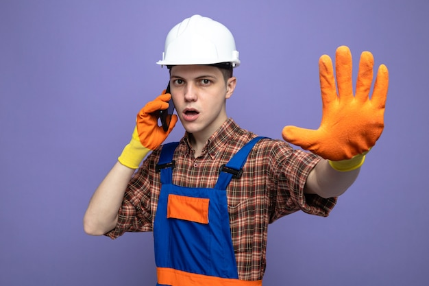 Construtor masculino rigoroso usando uniforme e luvas fala ao telefone