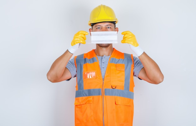 Construtor masculino segurando máscara médica sobre o rosto de uniforme, capacete, luvas, vista frontal.