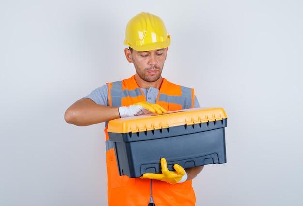 Construtor masculino tentando abrir a caixa de ferramentas de uniforme, capacete, luvas, vista frontal.