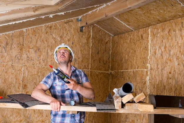 Construtor masculino, trabalhador da construção civil, segurando uma pistola de calafetagem e olhando para o teto dentro de uma casa inacabada com uma placa de madeira compensada de partículas expostas