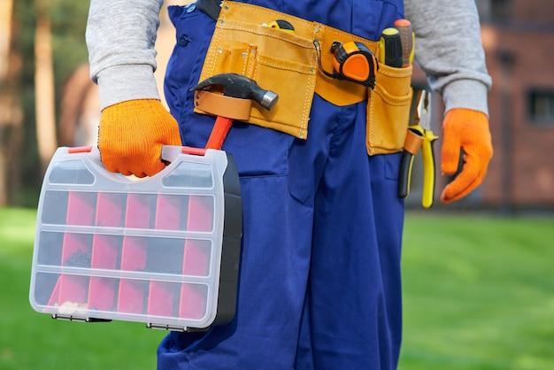 Construtor masculino usando cinto de ferramentas carregando caixa de ferramentas no canteiro de obras. close-up na área da cintura