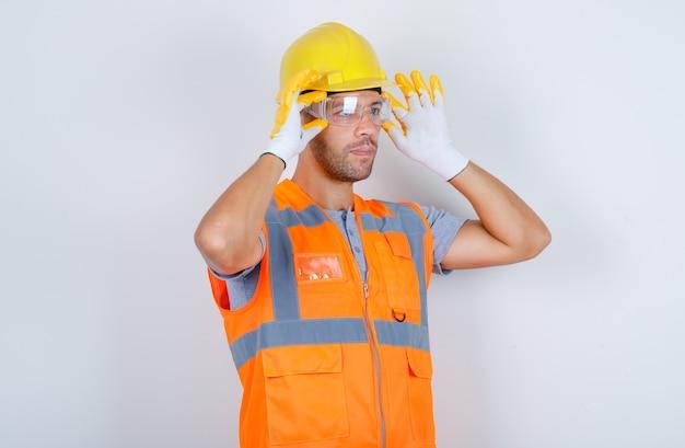 Construtor masculino usando óculos de segurança de uniforme, capacete, luvas, vista frontal.