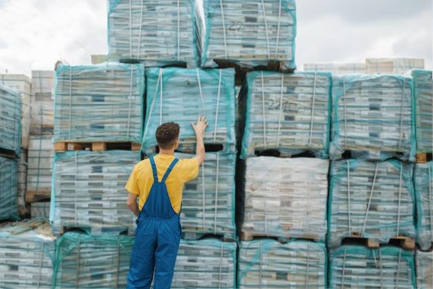 Construtor masculino verifica paletas com tábuas de madeira