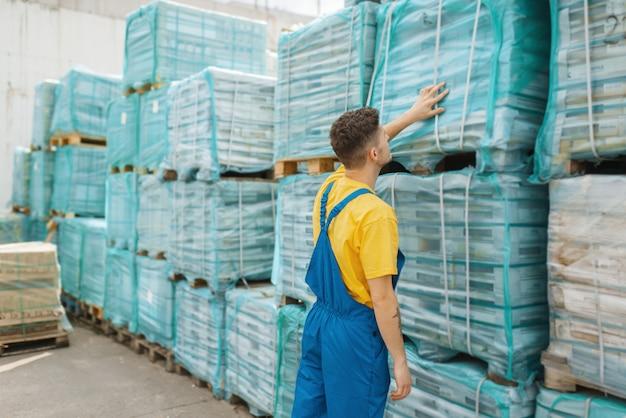 Construtor masculino verificar paletes com placas de madeira na loja de ferragens. construtor de uniforme olha as mercadorias na loja de bricolage