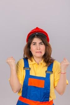 Construtor, mulher, desgastar, uniforme construção, e, capacete segurança, zangado, e, louco, levantando punhos, frustrado, e, furioso, com, cara zangada, isolado, parede branca