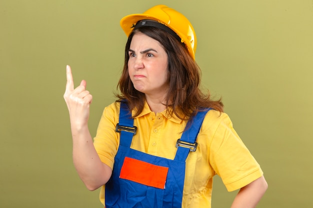 Construtor mulher vestindo uniforme de construção e capacete de segurança, apontando o dedo para cima olhando com reprovação para alguém sobre parede verde isolada