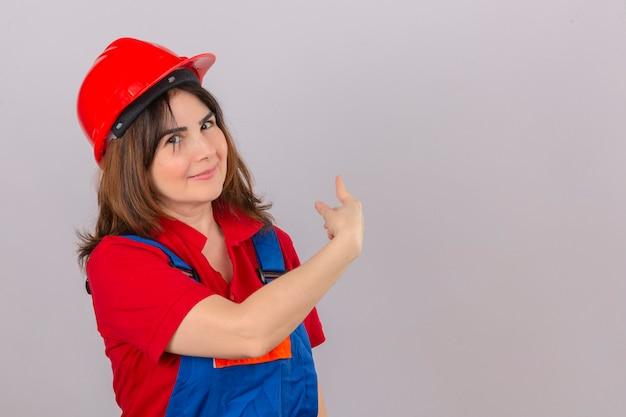 Construtor mulher vestindo uniforme de construção e capacete de segurança indicam algo no espaço em branco cópia atrás dela sobre parede branca isolada