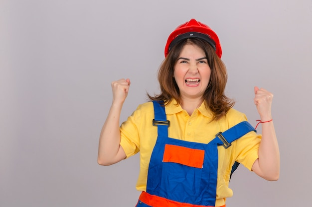 Construtor mulher vestindo uniforme de construção e capacete de segurança irritado e louco levantando os punhos frustrados e furiosos gritando com cara de brava sobre parede branca isolada
