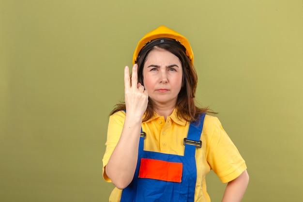 Construtor mulher vestindo uniforme de construção e capacete de segurança, mostrando e apontando os dedos número dois com expressão suspeita de pé sobre a parede verde isolada