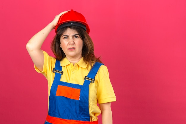 Construtor mulher vestindo uniforme de construção e capacete de segurança olhando mal com expressão triste tocando a cabeça tendo dor de cabeça sobre parede rosa isolada