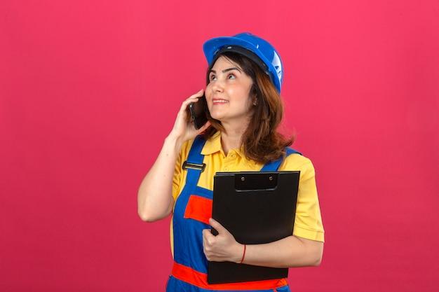 Construtor mulher vestindo uniforme de construção e capacete de segurança segurando a área de transferência enquanto fala no telefone móvel olhando para cima com sorriso no rosto sobre parede rosa isolada