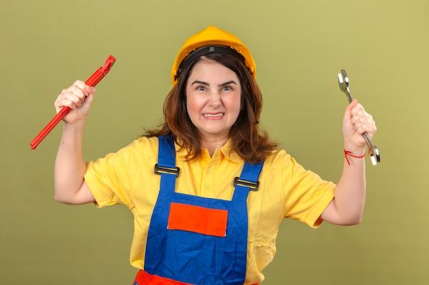 Construtor mulher vestindo uniforme de construção e capacete de segurança segurando as chaves nas mãos levantadas com expressão de raiva ao longo da parede verde isolada