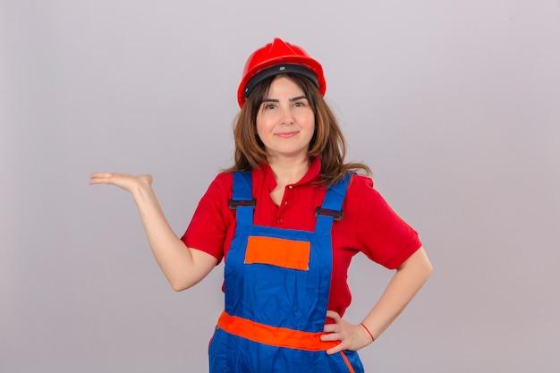 Construtor mulher vestindo uniforme de construção e capacete de segurança sorrindo alegre apresentando e apontando com a palma da mão, olhando para a câmera sobre parede branca isolada