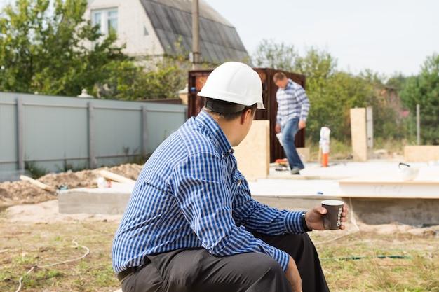 Construtor na pausa para o café sentado no canteiro de obras vendo seus colegas continuarem trabalhando