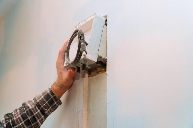 Construtor no trabalho. parede de corte de trabalho elétrico incluindo fios expostos