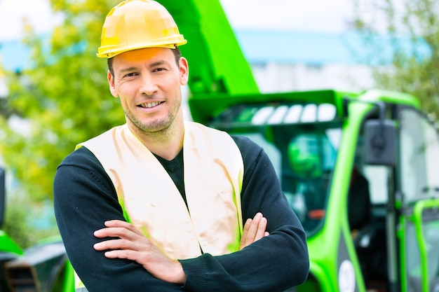 Construtor ou motorista em frente ao maquinário de construção no canteiro de obras