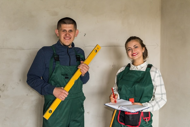 Construtor posando com instrumento de nível de água e mulher com bloco de notas