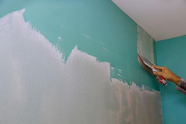 Construtor profissional alisa a parede com massa de espátula colocada em superfície nivelada de reparo de parede em seu próprio apartamento.
