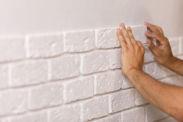 Construtor profissional colando azulejos decorativos na parede. trabalhador monta tijolos decorativos na parede