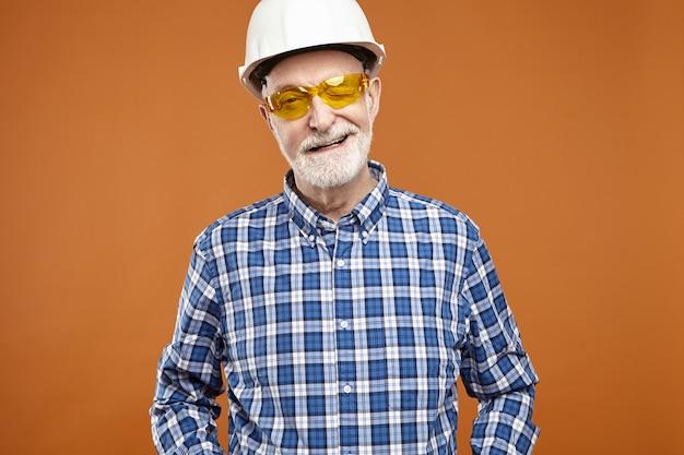 Construtor profissional de sucesso, homem barbudo, se aposentando, posando no estúdio usando capacete de segurança