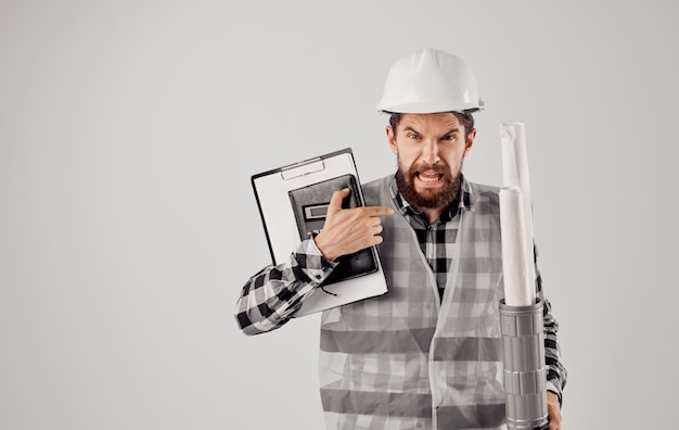 Construtor profissional em um capacete com um tubo nas mãos e documentos arquiteto-engenheiro